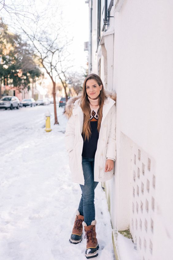a vintage-inspired sweater, blue jeans, a white puffed coat and hiking boots for snowy winter