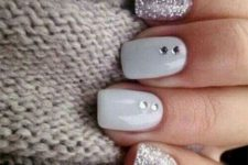 11 glossy white nails paired with silver glitter ones and rhinestones for a shiny winter-inspired look