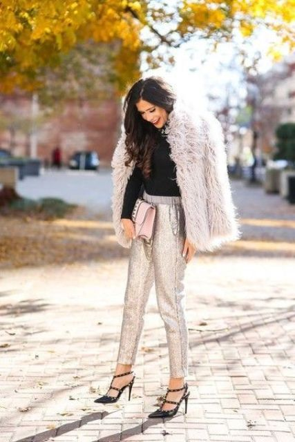 a holiday look with a black turtleneck, silver pants, black studded heels and a blush faux fur coat