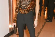 13 a one shoulder gold animal print top, black pants, black lacquer shoes and a box clutch