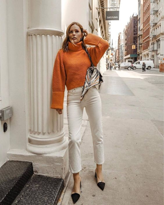 a vintage-inspired look with an orange cropped sweater, white straight jeans, two tone shoes and a bag