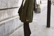 13 a white sweater, a dark green oversized jacket, black jeans, black hiking boots