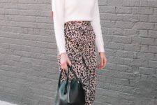 13 a white turtleneck sweater, a pink leopard print skirt, black sock boots, a black bag and red earrings