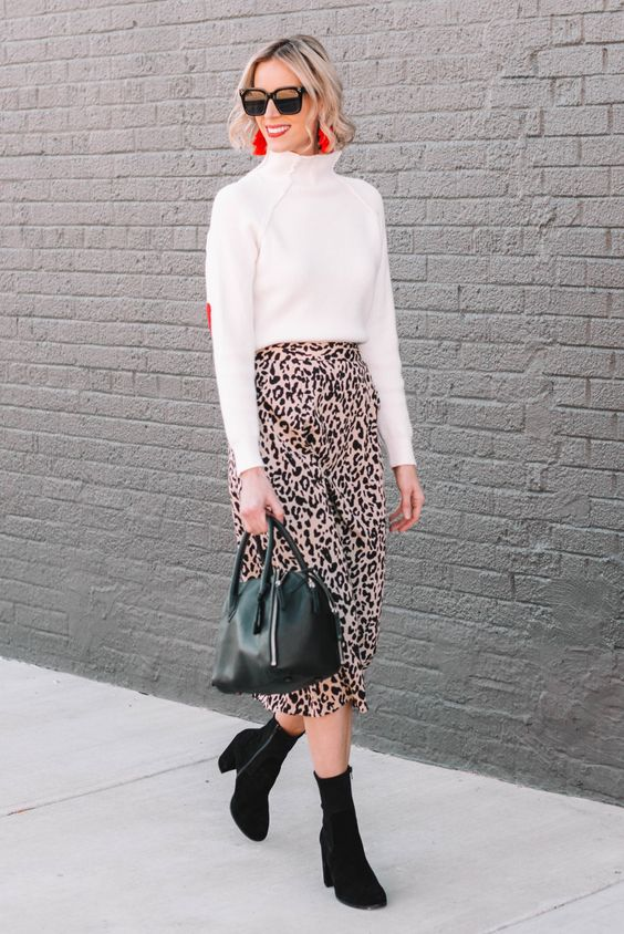 a white turtleneck sweater, a pink leopard print skirt, black sock boots, a black bag and red earrings
