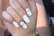 13 glossy white nails with shiny gold stripes for a modern and very bold look