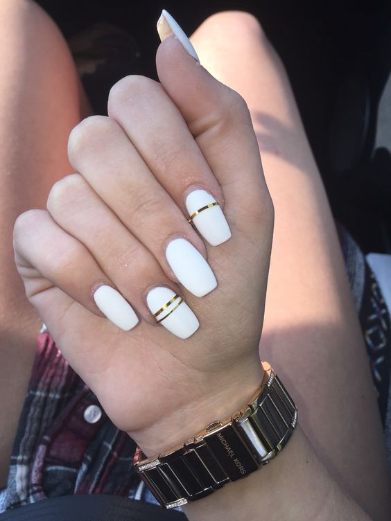 glossy white nails with shiny gold stripes for a modern and very bold look