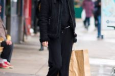 14 Gigi Hadid wearing a total black look of pants, a hoodie, a shearling coat and grey hiking boots