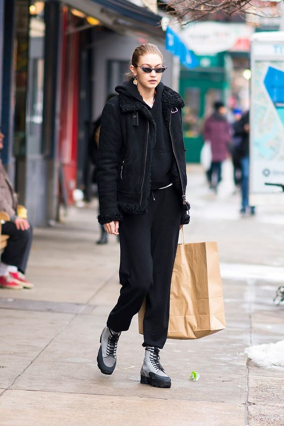 Gigi Hadid wearing a total black look of pants, a hoodie, a shearling coat and grey hiking boots