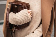 14 a neutral oversized sweater, a camel coat, black jeans and a brown snake leather bag