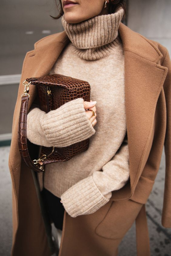 a neutral oversized sweater, a camel coat, black jeans and a brown snake leather bag