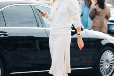 14 a white cashmere suit with a top and an asymmetrical skirt, tan tall boots and stylish accessories