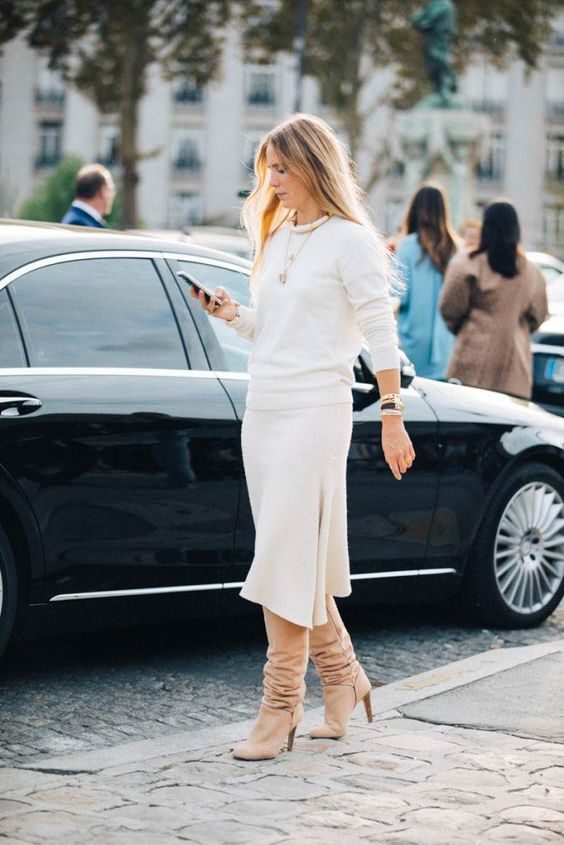a white cashmere suit with a top and an asymmetrical skirt, tan tall boots and stylish accessories