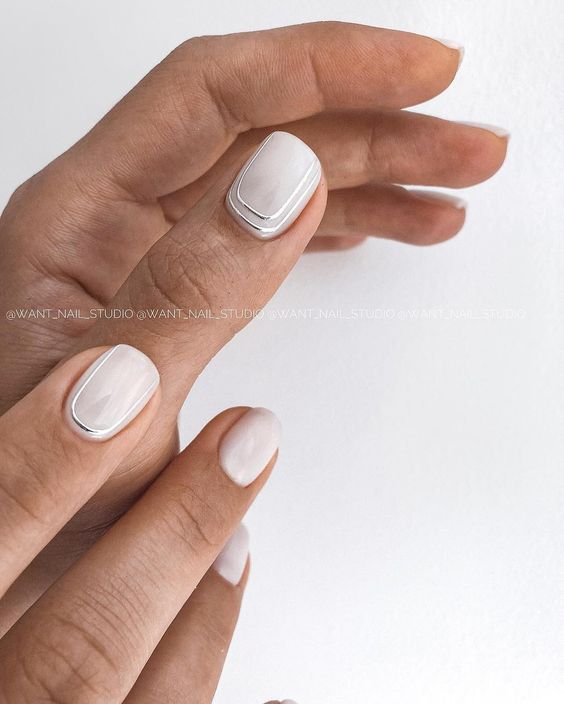 glossy white nails with silver stripes along two nails are a chic and refined idea