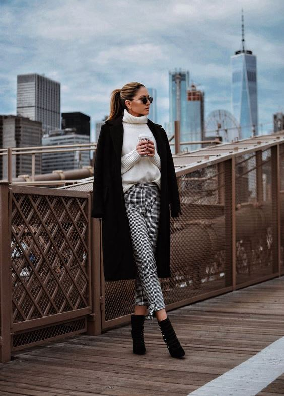 a stylish yet simple look with a white sweater, grey plaid pants, black booties with buttons and a coat