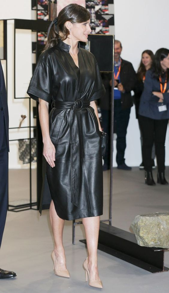 Queen Letizia wearing a black leather midi dress with pockets and a belt and nude shoes looks very chic