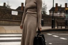16 a tan knit suit with an A-line midi skirt, black hiking boots and a black bag for an edgy winter look