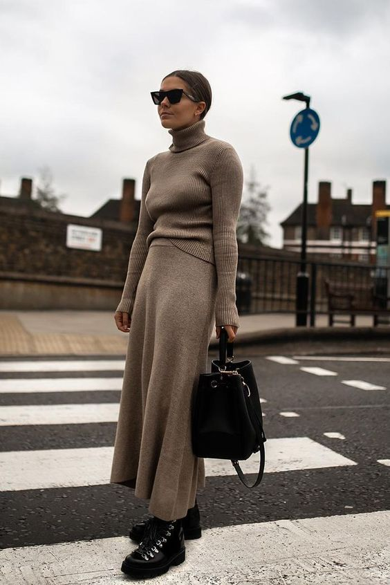 a tan knit suit with an A line midi skirt, black hiking boots and a black bag for an edgy winter look