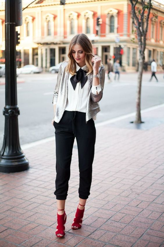 a white blouse with a black bow, a silver sequin cropped blazer, black pants and red shoes
