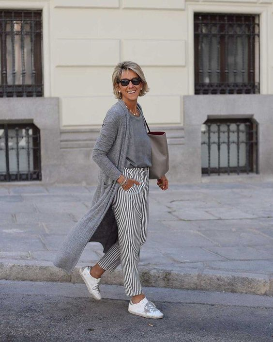 a fresh and lightweight monochromatic outfit with a tee, a cardigan, striped pants, white sneakers and a grey bag