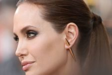 Angelina Jolie wearing a single large horn earring for a more modern and bold look