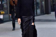 Gigi Hadid wearing a black slip midi dress, a black turtleneck sweater, blakc tall boots and a black bag
