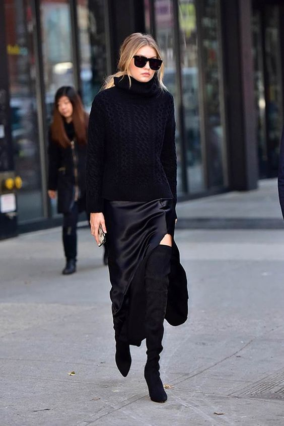 Gigi Hadid wearing a black slip midi dress, a black turtleneck sweater, blakc tall boots and a black bag