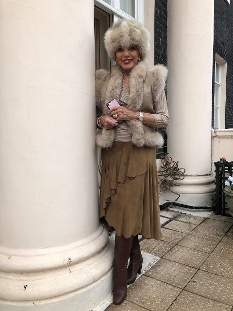 With beige sweater, fur vest, ruffled midi skirt and high boots