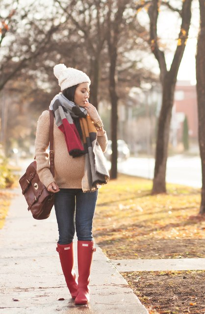 With beige sweater, skinny jeans, red high boots, brown leather bag and white pom pom hat