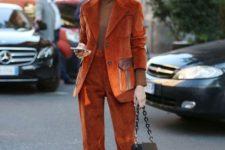 With beige turtleneck, orange suede suit, brown cap and brown boots