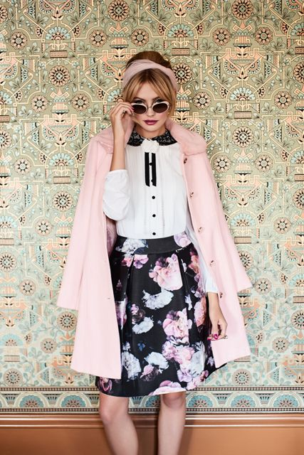With black and white blouse, floral knee length skirt and sunglasses