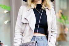 With black crop top, wide brim hat, gray trousers and beige trench coat
