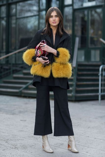 With black flare pants, floral clutch and light gray boots
