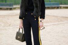 With black turtleneck, fur vest and small bag