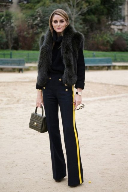 With black turtleneck, fur vest and small bag