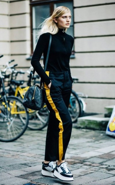 With black turtleneck, platform sneakers and printed bag