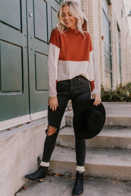 With black wide brim hat, dark colored jeans and black ankle boots