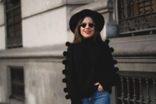 With black wide brim hat, pom pom sweater and jeans