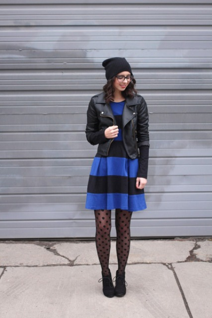 With blue and black striped dress, black hat, black leather jacket and lace up boots