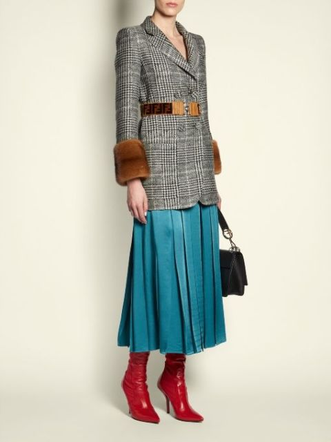 With blue pleated midi skirt, brown belt, black bag and red boots