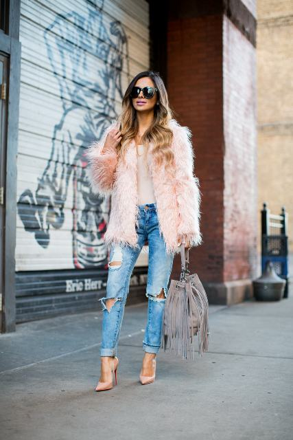 With distressed jeans, high heels, sunglasses and fringe bag