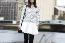 With geometric printed sweatshirt, black bag, black tights and white flat shoes