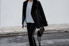 With gray sweater, black jacket, wide brim hat, black bag and boots