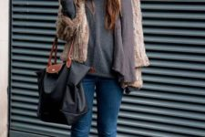 With gray sweatshirt, skinny jeans, green lace up flat boots, fur jacket and tote bag