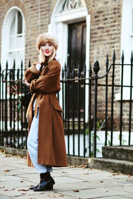 With light blue cuffed jeans, brown maxi coat and black boots
