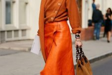 With orange loose sweater, orange leather midi skirt and low heeled shoes