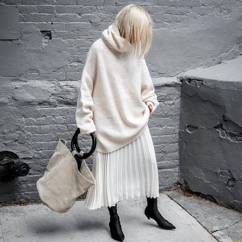 With oversized sweater, tote bag and black low heeled boots