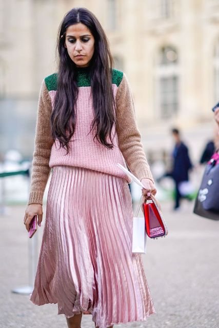 With pale pink pleated midi skirt and small bag