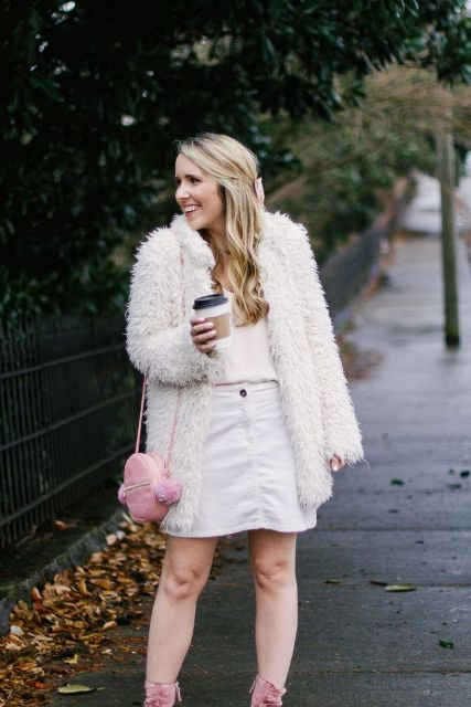 With pale pink shirt, faux fur coat, pink bag and pink boots