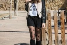 With t-shirt, beige and black leather jacket, black shorts and brown boots