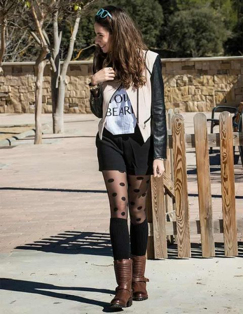 With t shirt, beige and black leather jacket, black shorts and brown boots